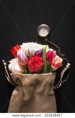Old pocket watch and colorful flowers - Beautiful bouquet of diverse flowers wrapped in a rustic jute sack and a vintage pocket clock, on a black background, on a sunny day of spring.