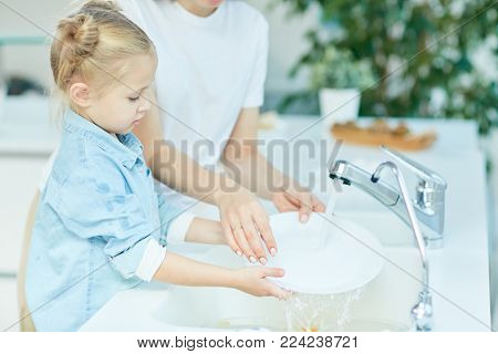 Little girl helping her mother wash dishes over sink in the kitchen after dinner