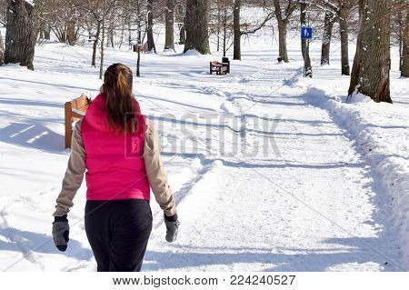 Young woman walking in the park on beautiful winter day.