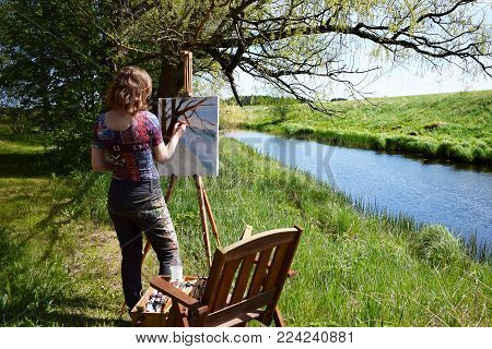 Woman artist paints landscape painting of small river. Painter rear view.