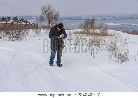 Mature man checking cellular phone while walking on a snowy road near  frozen Dnipro river in Ukraine