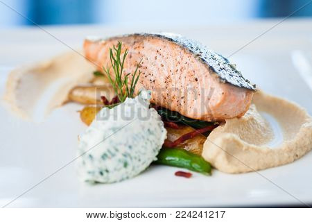 Baked salmon with roasted cauliflower cream, almond potatoes, peas-chorizo salad and cream cheese-herb sauce