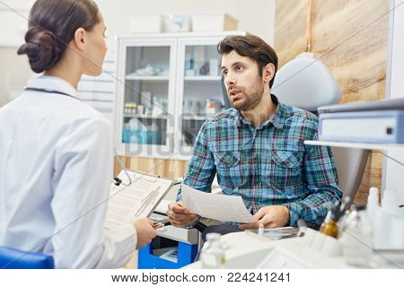 Male patient talking to young clinician in modern clinics during appointment