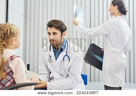 Young doctor listening to little patient while his assistant on background learning x-ray images