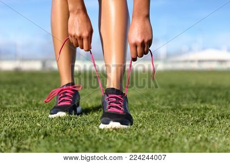 Running and fitness exercise sport girl getting ready tying shoes jogging on park grass. Summer active lifestyle.
