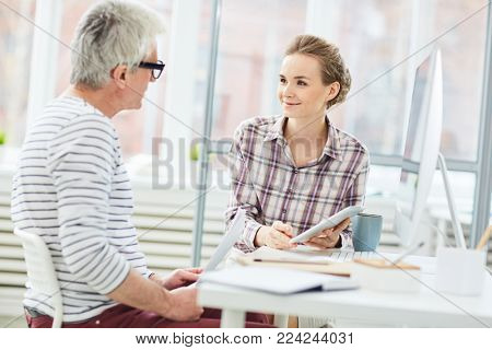 Girl with touchpad looking at her employer and listening to his comments about new project