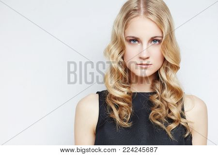 Portrait of sensual blond woman with curly hair over light grey background.