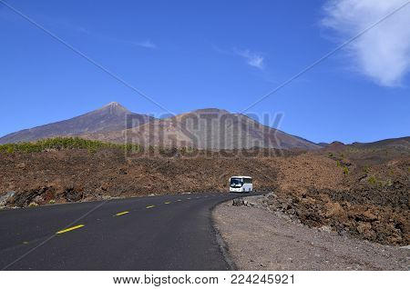 Road towards volcano El Teide with tourist bus driving through Teide National Park,Tenerife.Mount Teide is the Canary Islands most visited tourist attraction.