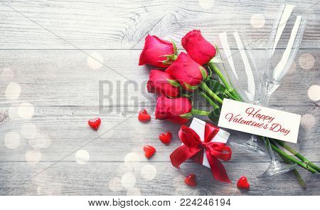 Valentines day greeting card, gift box, red roses and champagne flutes on wooden table. Top view with copy space