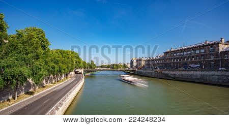 Wide angle long exposure view of blurred tourist boat over Seine river and road, Paris