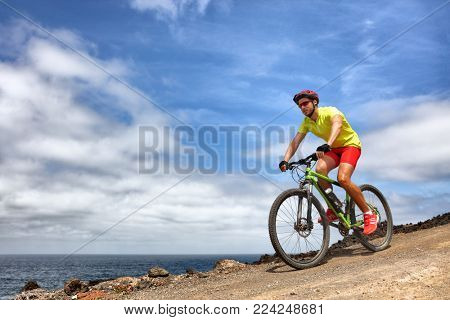 Mountain bike sport man riding MTB bicycle. Biking fitness athlete cyclist on mountain trail in summer outdoors. Sport health lifestyle.
