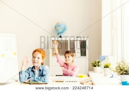 Pretty schoolgirl and her classmate raising hands at lesson to answer by blackboard