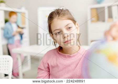 Calm schoolchild looking at globe model at school before lesson of geography