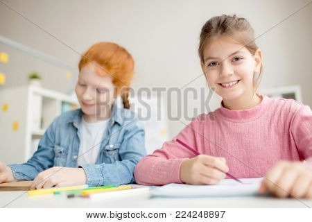 Cute girl with toothy smile looking at camera at lesson with her classmate near by