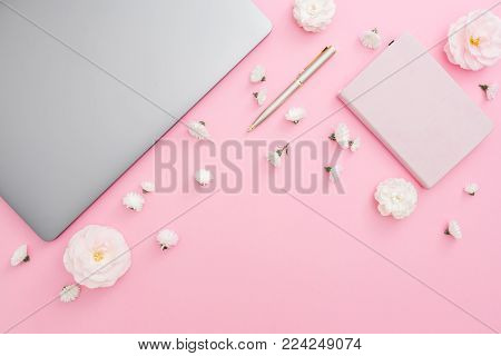 Stylish office desk with laptop, notebook, pen and flowers on pink background. Top view. Flat lay lifestyle concept.