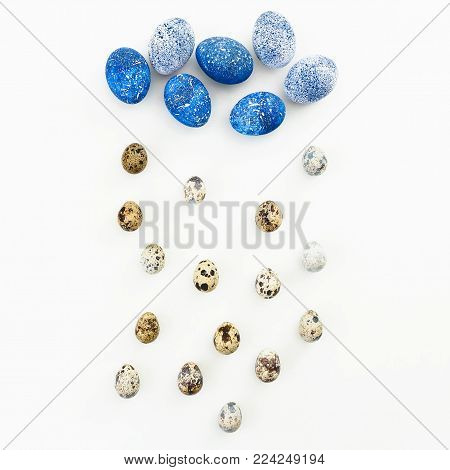 Blue Speckled Easter Egg with quail eggs on white background. Flat lay. Top view. Cloud and rain made of easter eggs.