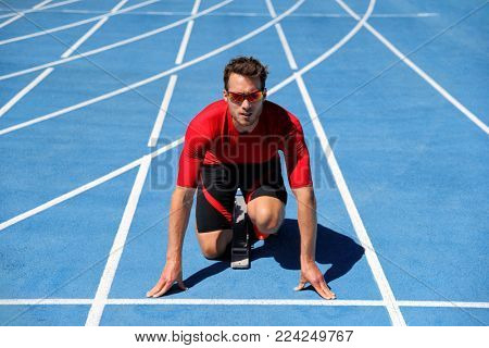 Runner athlete starting running at start of run track on blue running tracks at outdoor athletics and fiel stadium. Sport and fitness man running in run race competition.