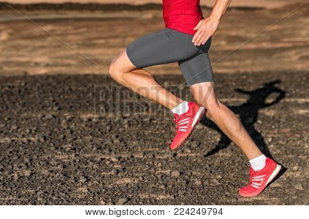 Running shoes sport athlete runner man running on trail landscape terrain. Healthy active lifestyle young adult person jogging in summer outside nature. Closeup of legs, feet.