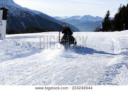 Ski resort staff member driving snowmobile. Ski resort in Italy Alps