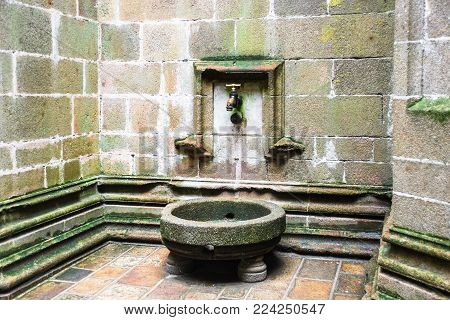 LE MONT SAINT-MICHEL - JULY 5, 2010: outdoor water tap in court of Saint Michael Abbey. Le Mont Saint-Michel is an island commune in Normandy, first monastic on the mount was built in the 8th century
