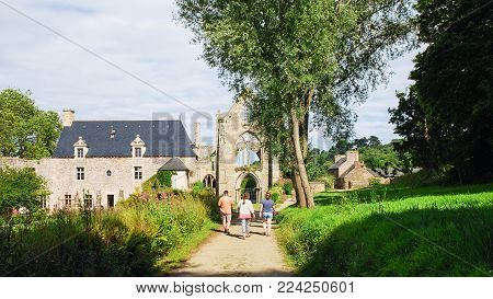 PAIMPOL, FRANCE - JULY 4, 2010: tourists walk to ruined church of Abbaye de Beauport (abbey) in Kerity district of Paimpol town in Cotes-d'Armor department of Brittany in summer sunny day