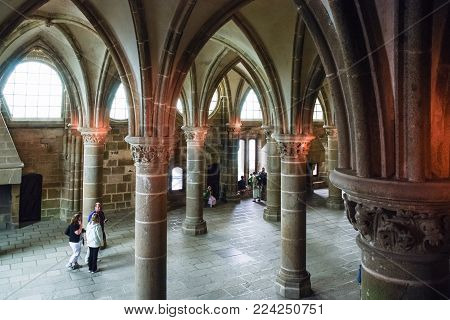 LE MONT SAINT-MICHEL - JULY 5, 2010: visitors in hall of Saint Michael's Abbey. Le Mont Saint-Michel is an island commune in Normandy, first monastic on the mount was built in the 8th century