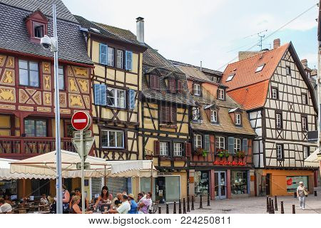 COLMAR, FRANCE - JULY 11, 2010: people in outdoor cafe near medieval fachwerk houses on square Place des Martyrs de la Resistance in Colmar. Colmar is the third-largest commune of Alsace region