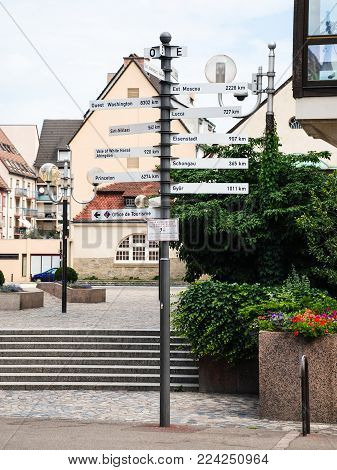 COLMAR, FRANCE - JULY 11, 2010: geographic sign with travel distance to cities on square Place de la Mairie in Colmar city. Colmar is the third-largest commune of Alsace region