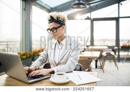 Young elegant businesswoman working in the net while sitting in cafe
