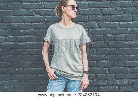 Summer day. Front view. Young millennial woman dressed in gray t-shirt is stands against dark brick wall. Mock up. Space for logo, text, image.
