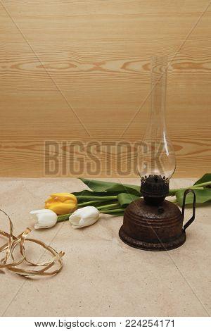 old kerosene lamp and spring tulips on a light background