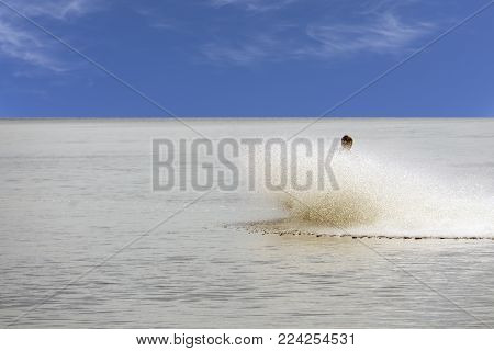 Girl falling jumping into the water with big splash. Nature recreation concept