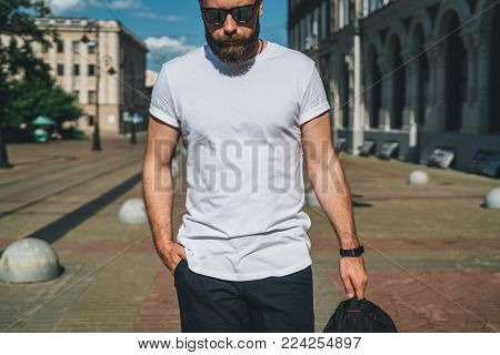 Summer day. Front view. Young bearded millennial man dressed in white t-shirt and sunglasses is stands on city street. Mock up. Space for logo, text, image. Instagram filter, film effect, bokeh effect.