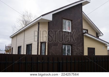 Curb appeal of brand-new home in brown and beige colors with two garages and concrete driveway. Northwest