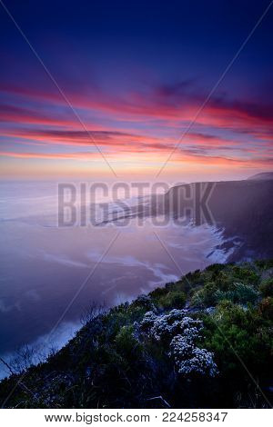 Dreamy, dramatic and colourful sunset over Storms River Mouth national park, South Africa. Long exposure with blurred water