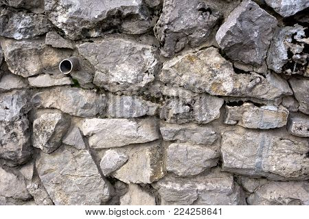 Single water pipe protruding from a cracked white plaster wall with surface cracks and fissures