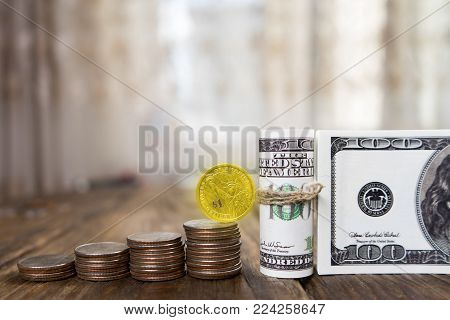One hundred dollars banknotes of the stack of coins from quarters and one dollar.