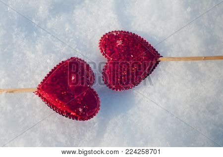 Two red hearts on wooden sticks laying opposite each other on white winter snow. Top view