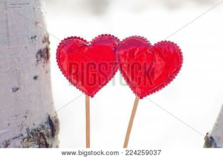 Two red foil hearts staying against white winter background. Love decorations