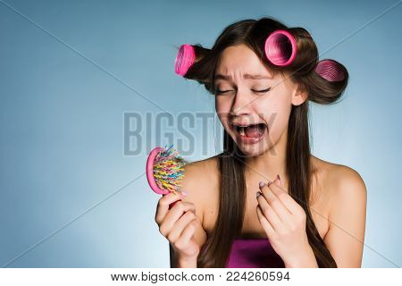 sad young girl can not make a hairdress, head curlers, crying, losing hair
