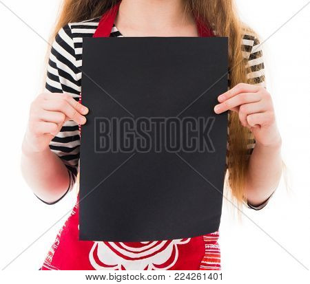 Close-up of chilld's hands holding vertical blank sheet of paper for your menu, recipe, text, advertising, promotions isolated on white background. Black backgrund for text, recipe, copyscpace