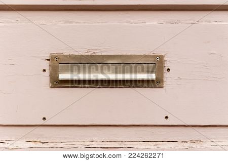 Old letterbox or mailbox in the wooden gate door traditional way of delivering letters or mail to the house address close up