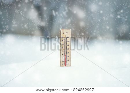 The thermometer in the snow, shows the temperature of Zero during the time of the Snow Storm. Winter. Snow storm. Snowfall.