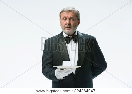 Senior waiter holding tray with cup and standing isolated on white studio background. concept of good service