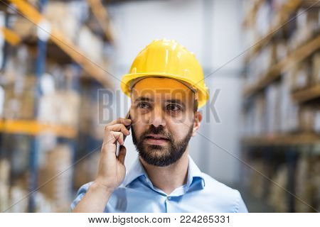 Warehouse worker or supervisor with a smartphone, making a phone call.