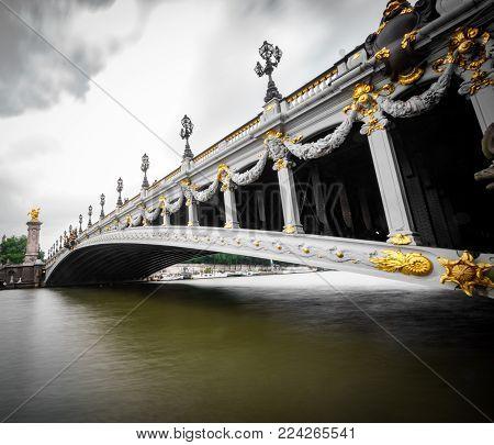 Long exposure silk water and wide angle view of Alexandre III Bridge in Paris