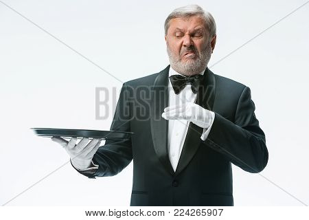 The senior waiter holding tray man with a grimace of disgust on his face and standing isolated on white studio background. concept of bad food