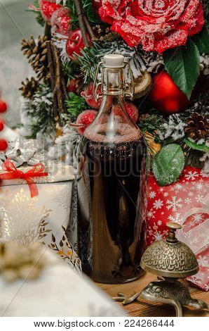 Christmas hot mulled wine with cinnamon, bottle of red on background christmas tree. Close up, copy space. Food and drink, seasonal and holidays concept. Christmas new year hot warm beverage