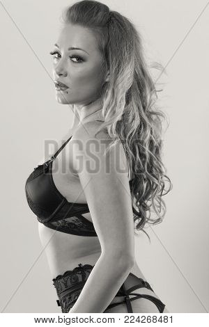 Beauty and sexiness of female body. Attractive seductive young woman in black lingerie. Portrait of sexy gorgeous and provocative girl.