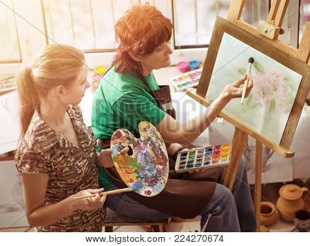 Artist painting easel in studio. Authentic children girl paints with set palette watercolor paints palette and brush in morning sunlight . Top view indoor home interior handmade crafts with window .